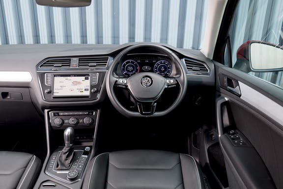 The interior of a Volkswagen Tiguan with steeringwheel and dashboard in shot