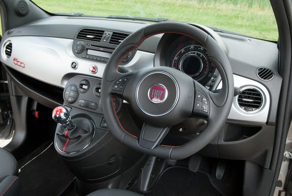 The interior of a Fiat 500 with steeringwheel and dashboard in shot