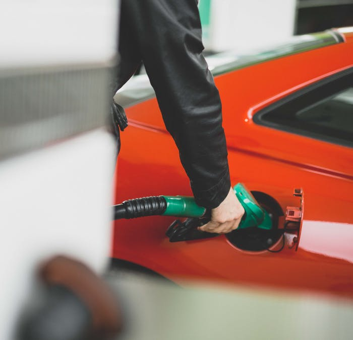Person putting petrol into a red car.