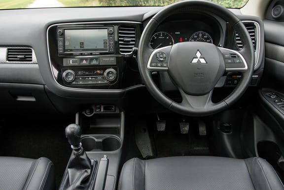 The interior of a Mitsubishi Outlander with steering wheel and dashboard in shot