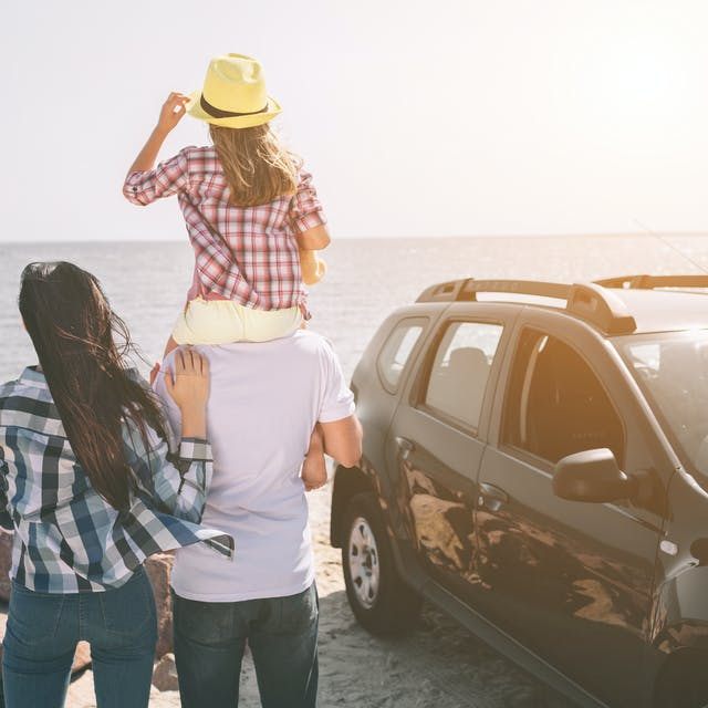 Family at the beach with their car