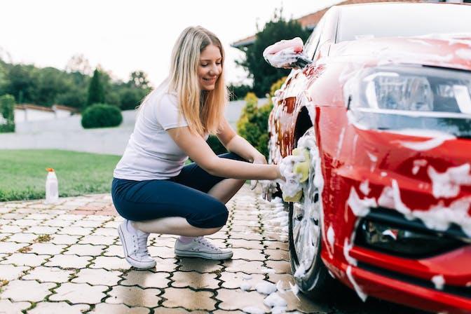 Woman washing red car