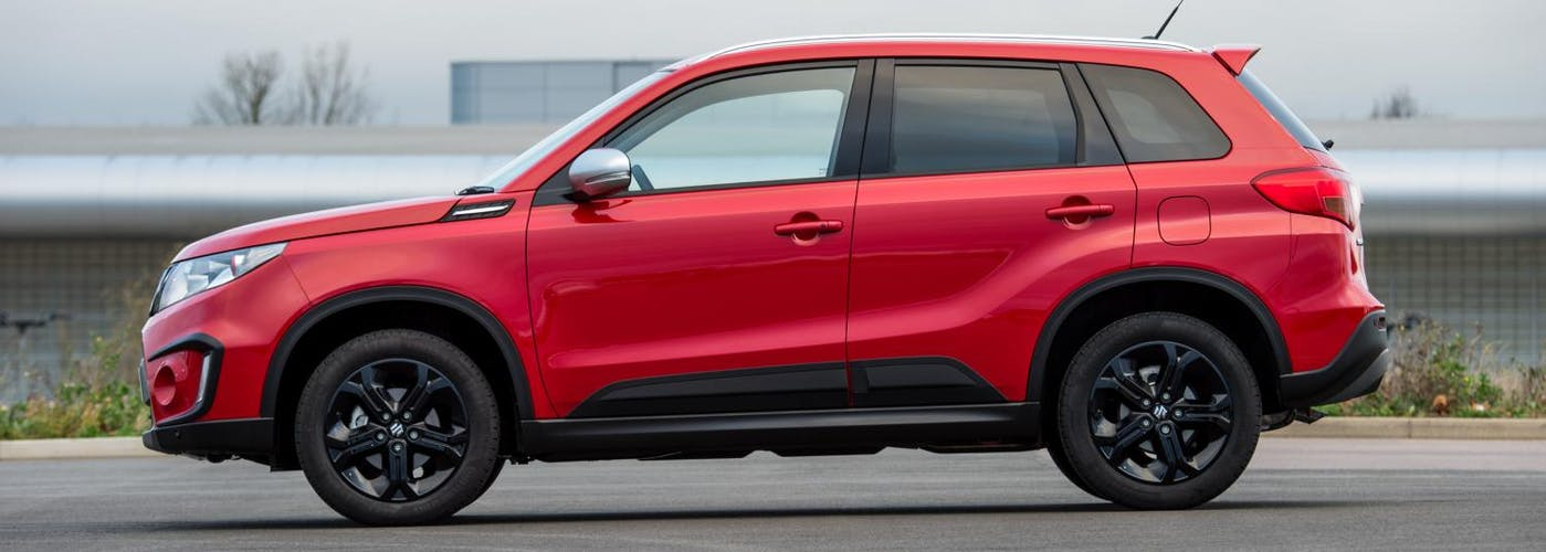 The side exterior of a red Suzuki Vitara