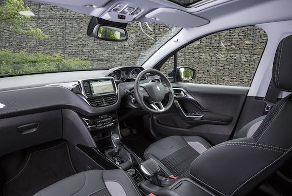 The interior of a Peugeot 2008 with steeringwheel and dashboard and front seat in shot