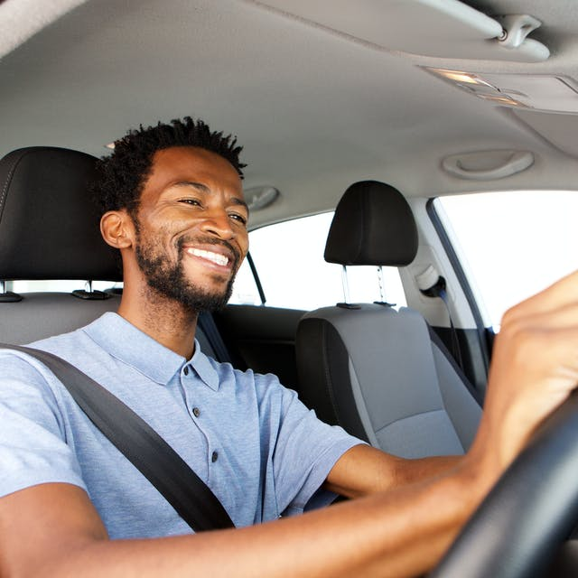 Smiling man driving a car