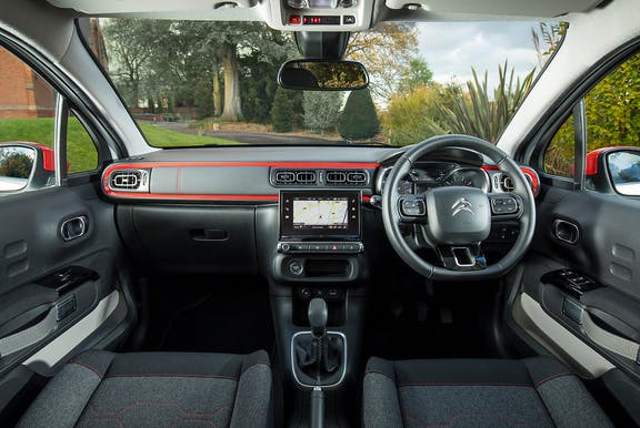 The interior of a Citroen C3 with steering wheel and dashboard in shot