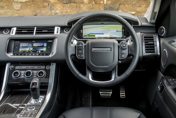 The interior of a Range Rover Sport with steering wheel and dashboard in shot