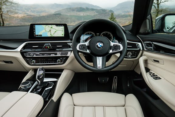 The interior of a BMW 5 Series with steeringwheel and dashboard in shot