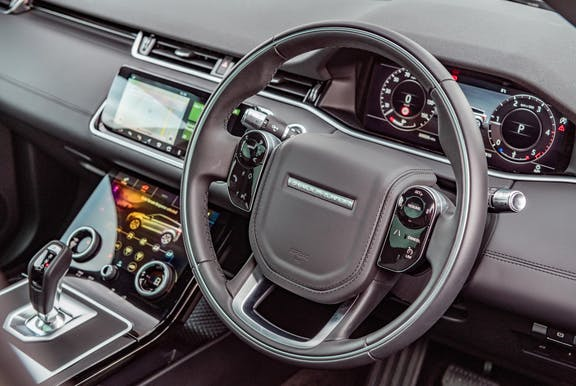 The interior of a Range Rover Evoque with steeringwheel and dashboard in shot