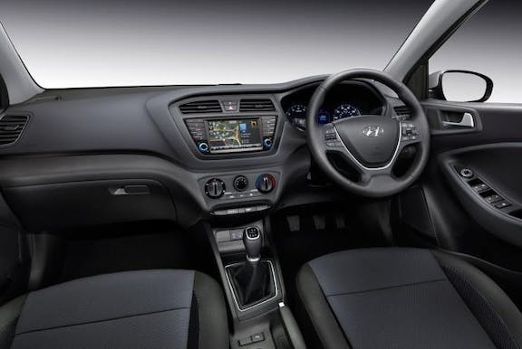 The interior of a Hyundai i20 with steeringwheel and dashboard in shot