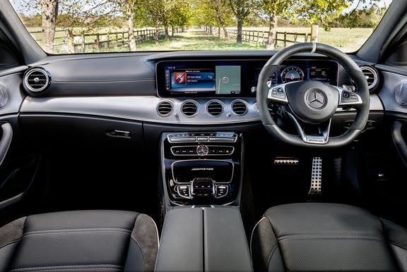 The interior of a Mercedes-Benz E-Class with steering wheel and dashboard in shot