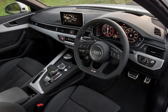 The interior of an Audi A4 with steering wheel and dashboard in shot