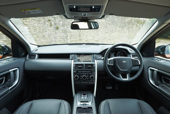 The interior of a Land Rover Discovery Sport with steeringwheel and dashboard in shot