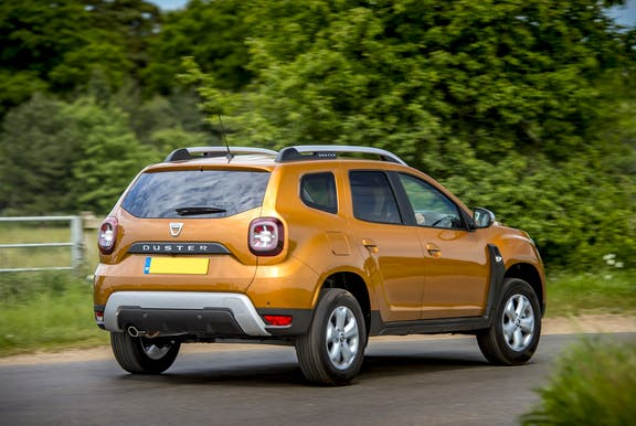 The rear exterior of a gold Dacia Duster