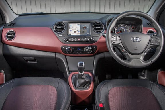 The interior of an Hyundai i10 with steering wheel and dashboard in shot