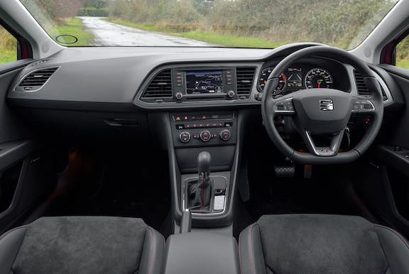 The interior of a Seat Leon with steering wheel and dashboard in shot
