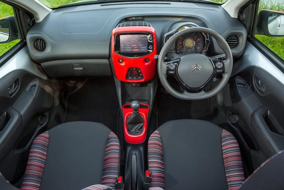 The interior of a Citroen C1 with steeringwheel and dashboard in shot