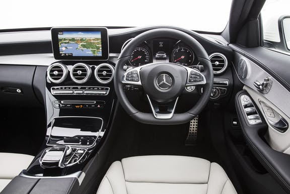 The interior of a Mercedes-Benz C-Class with steering wheel and dashboard in shot