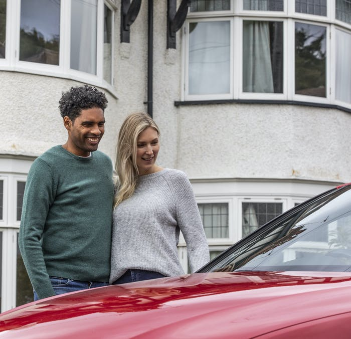 Happy couple looking at their new car from Cazoo