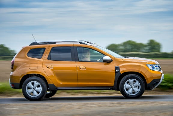 The side exterior of a gold Dacia Duster