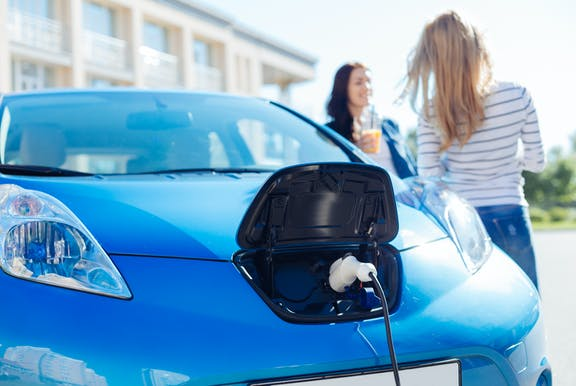 Blue electric car being charged