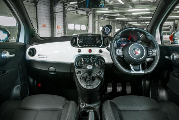 The interior with dashboard and wheel of an Abarth 595