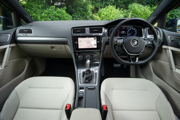 The interior of a Volkswagen Golf with steering wheel and dashboard in shot