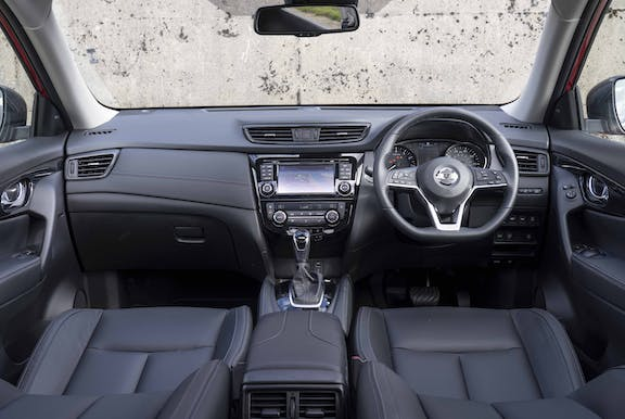 The interior of a Nissan X-Trail with steeringwheel and dashboard in shot