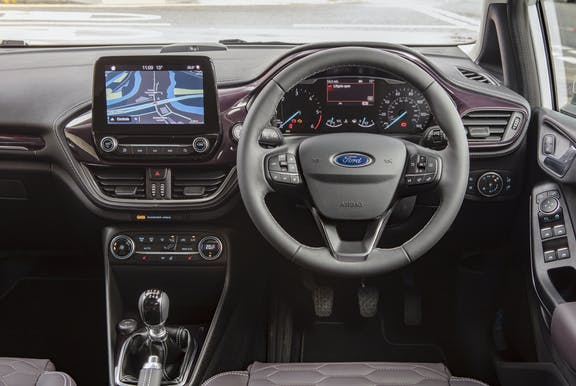 The interior of a Ford Fiesta with steeringwheel and dashboard in shot