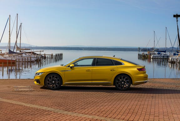 The side exterior of a yellow Volkswagen Arteon