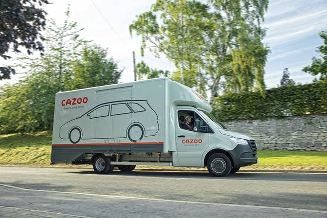 A Cazoo transporter delivering a car
