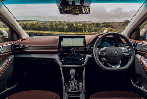 The interior of a Hyundai Ioniq with steering wheel and dashboard in shot