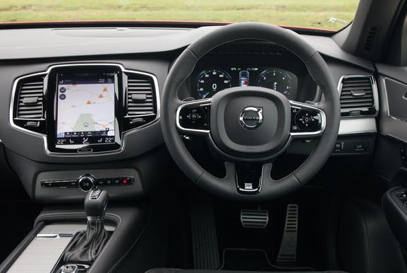 The interior of a Volvo XC90 with steering wheel and dashboard in shot