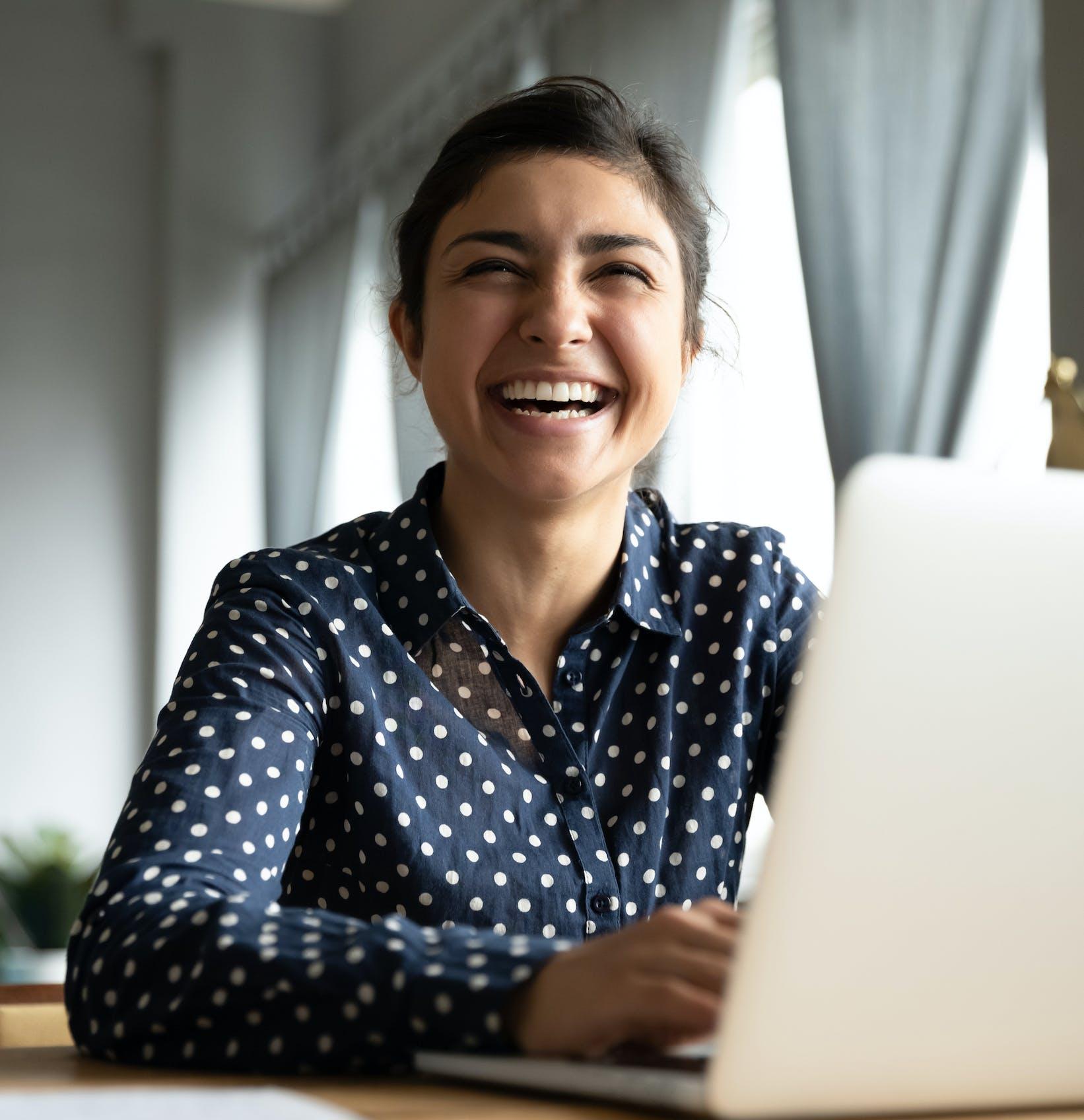Woman on laptop laughing