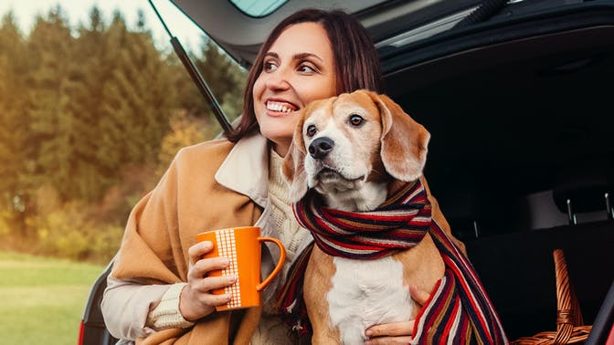 Lady sipping a hot drink with her dog in the back of a car