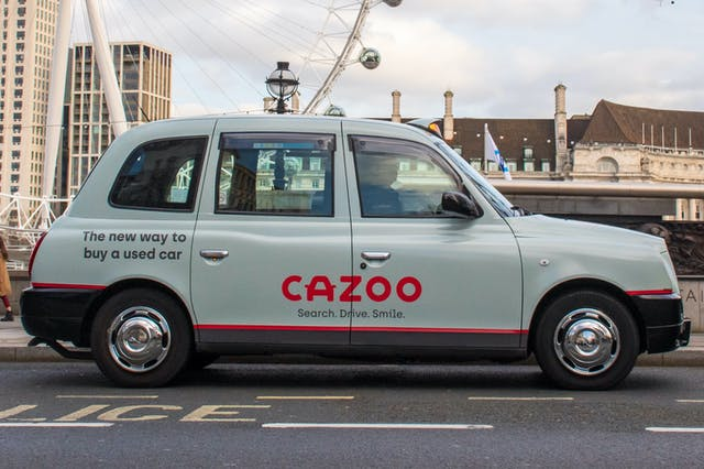 A London taxi with Cazoo advertising. The new way to a buy a used car.