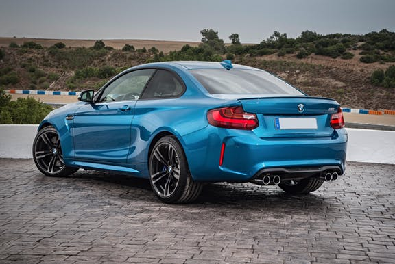 The rear exterior of a blue BMW M2