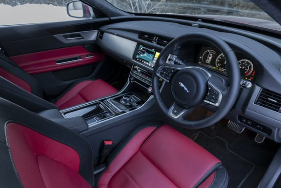 The interior of a Jaguar XF with steering wheel and dashboard in shot