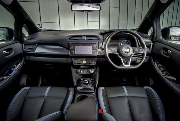 The interior of a Nissan Leaf with steering wheel and dashboard in shot