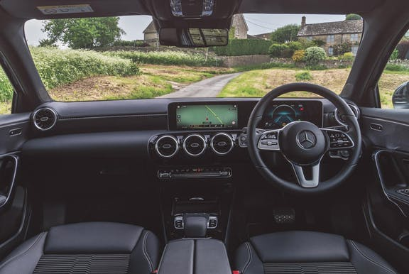 The interior of a Mercedes-Benz A-Class with steering wheel and dashboard in shot