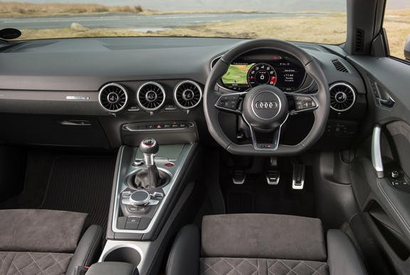 The interior of an Audi TT with steering wheel and dashboard in shot