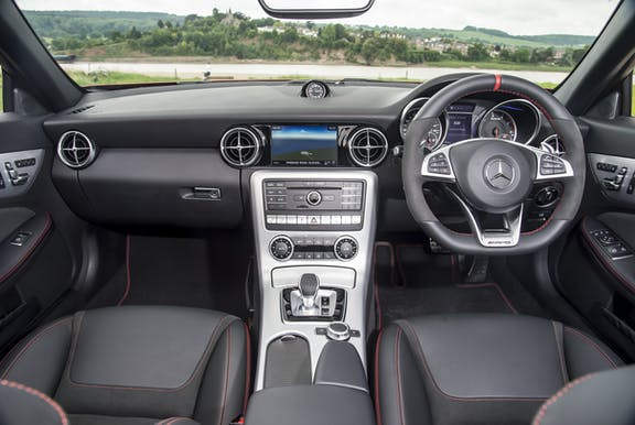 The interior of a Mercedes-Benz SLC with steering wheel and dashboard in shot