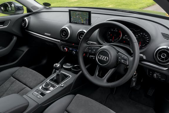 The interior of an Audi A3 with steering wheel and dashboard in shot