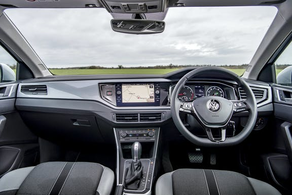 The interior of a Volkswagen Polo with steering wheel and dashboard in shot