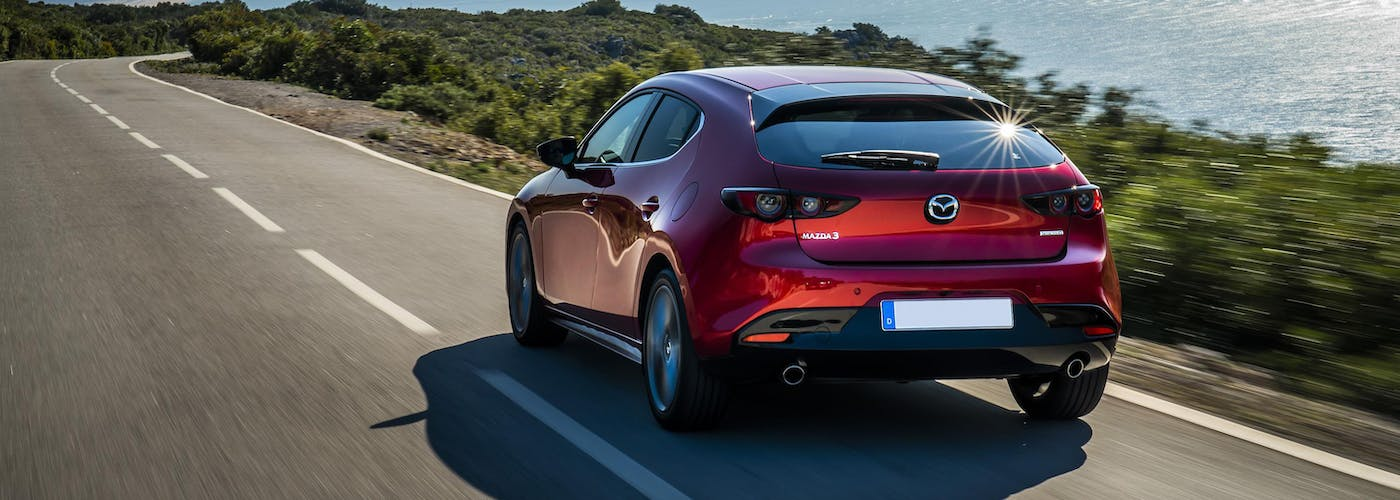 The rear exterior of a red Mazda 3
