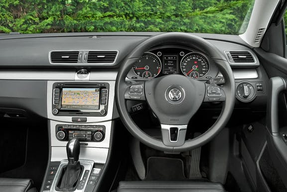 The interior of a Volkswagen Passatwith steering wheel and dashboard in shot