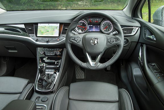 The interior of a Vauxhall Astra with steering wheel and dashboard in shot