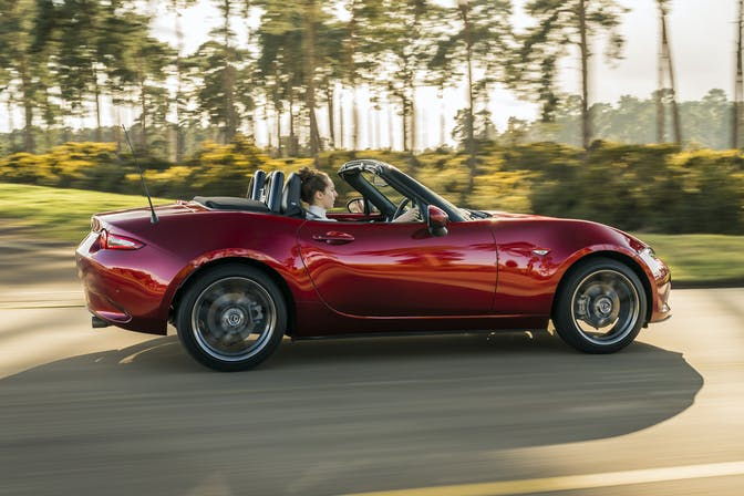 The side exterior of a red Mazda MX-5