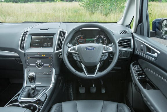 The interior of a Ford S-Max with steeringwheel and dashboard in shot