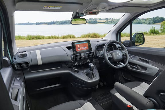 The interior of a Citroen Berlingo with steering wheel and dashboard in shot